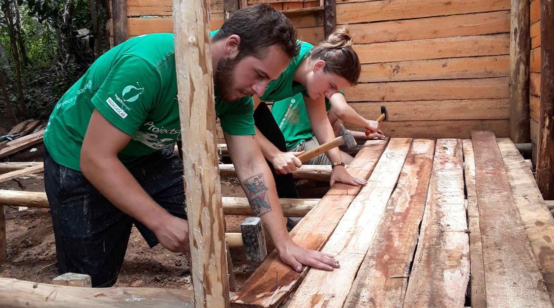 Voluntarios de construcción ayudando a preparar una estructura.